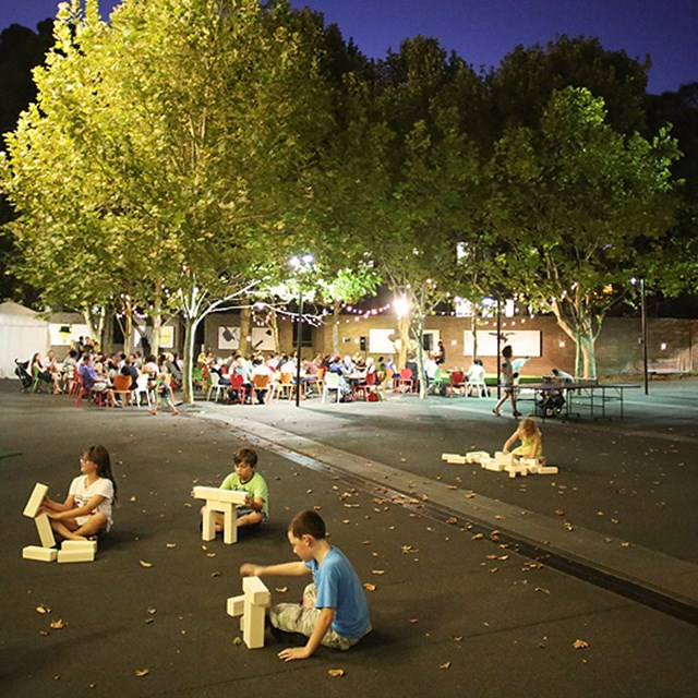 Children playing with building blocks in outdoor courtyard event space at night.